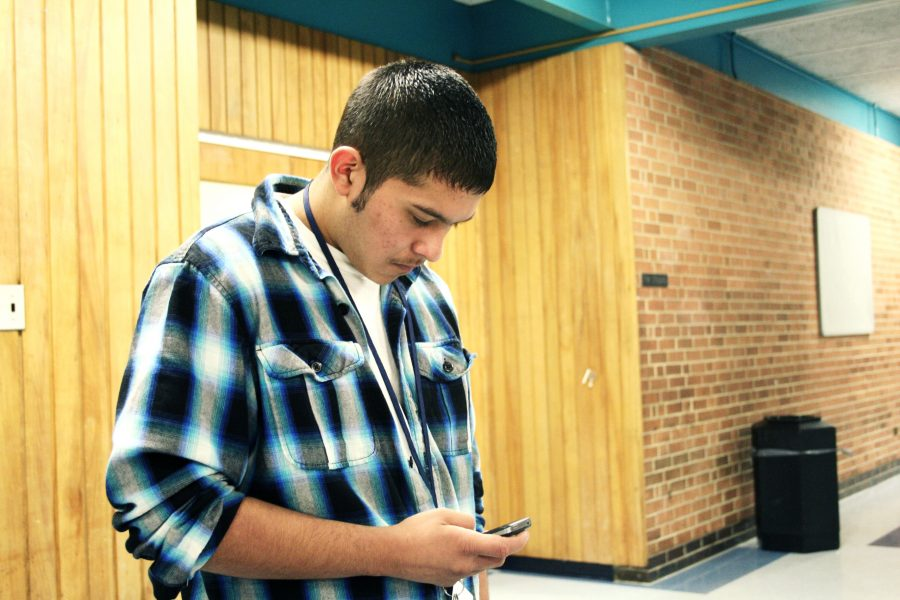 Gerado Saucedo checks his social networks on his phone. Photo by Miki Patel