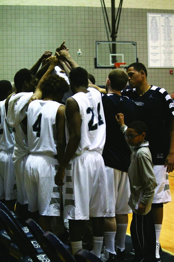 The Loy Norrix men's varsity basketball team huddles after a timeout. The Knights believe the teamwork is the key to success. l