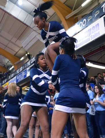Senior Latroia Atkins is lifted to the top of the pyramid by fellow cheerleaders at the Kalamazoo Central game. The competitive cheer team has had a strong season. Photo by Racheal Koole.