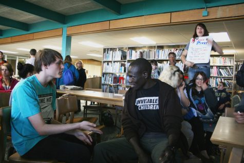 Ugandan Richard Olunya speaks with Dakota Dunn as Great Lakes Region representative Briana Santos tells students the Michigan senators numbers. Over 115 calls were made to several senators in the library during third lunch. Photo by Racheal Koole
