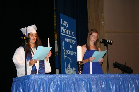 Senior class president Marta Grabowski passes the torch of leadership to Junior class president Sarah Townsend. The candlelight ceremony not only awards those who have excelled in certain areas, but recognizes the upcoming seniors.