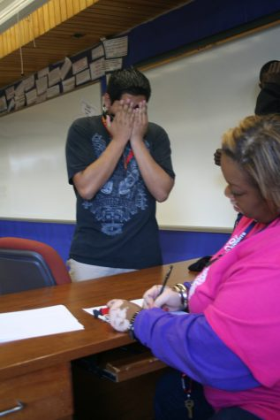 Fernando Juarico-Cervantes hides his face as DaNetta Blake signs him in to Hall Sweep. She tells him to take a seat in the fourth row, fourth seat. Cervantes sits among 16 other students at 1:20 pm. Photo by Allie Creamer