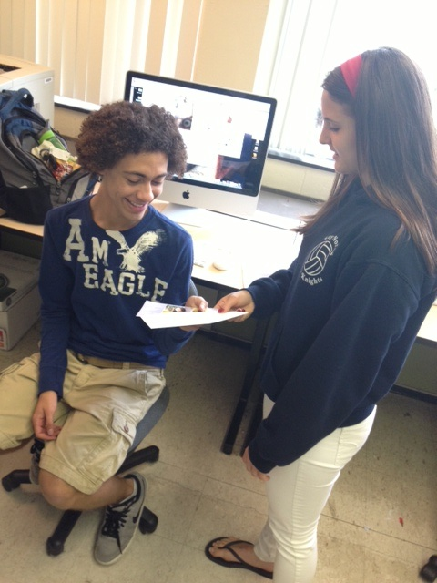 Photo by Mia Leibold  Senior Erin Romph and Josh Johnson exchange graduation invitations in class. They are both having celebrations at their homes in June.