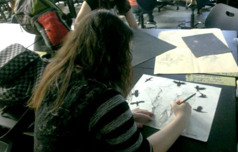 Photo By Sha'Kira Green Junior Kailee Mcdade works on her next charcoal piece. This piece was consists of the ravens she uses in her other works,