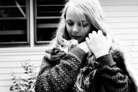 Iris Tanja hugs a kitten named Ramona. Tanja is an avid reader, as well as a serial cat cuddler.  Photo Credit: Jazz Porter