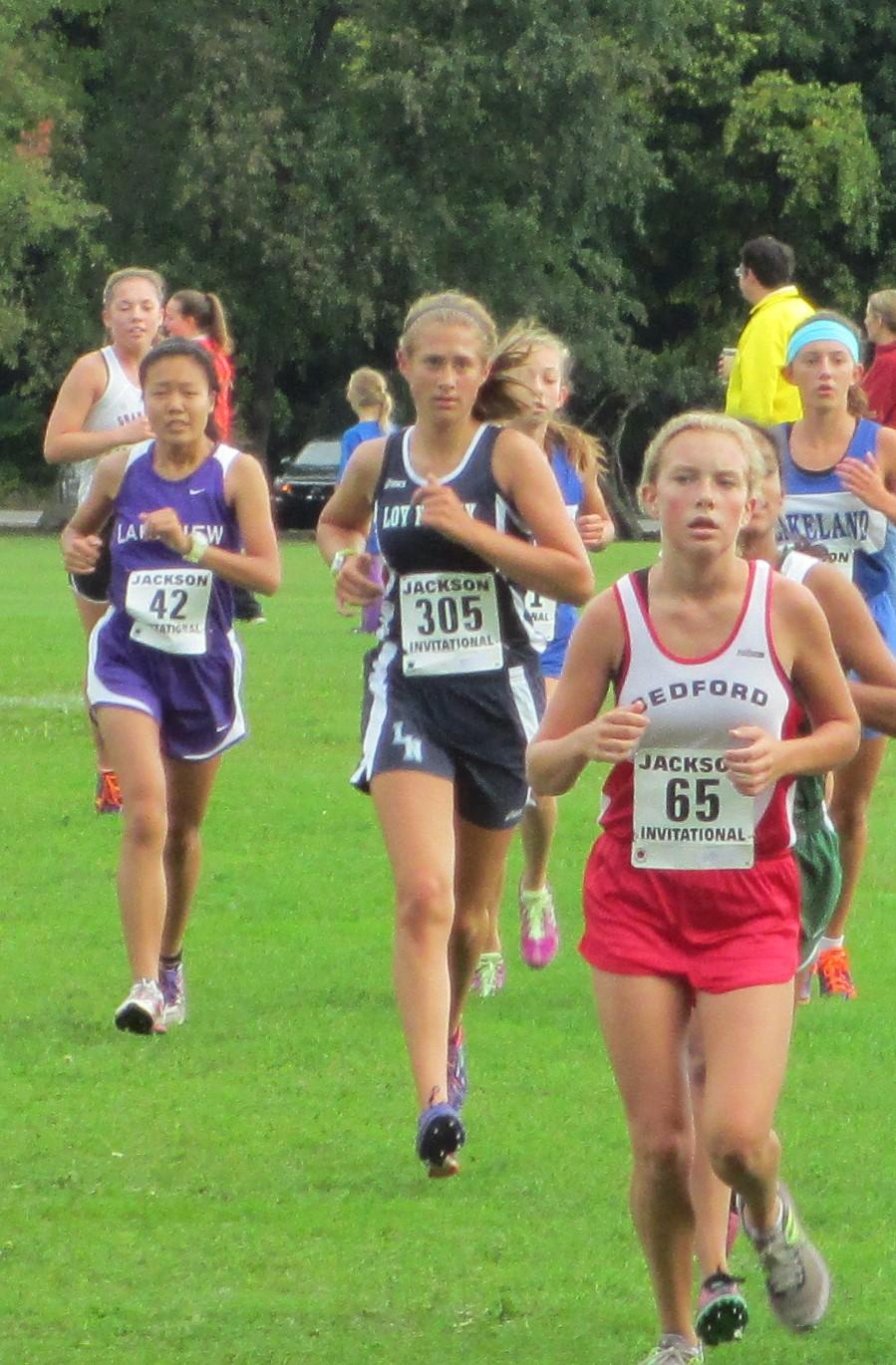 Sophomore Olivia Vande Pol, (center) running in a cross country meet for Loy Norrix Highschool. She is hoping to beat her personal best mile time of 6:30.