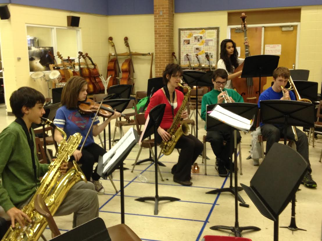 """Orchestra teacher and conductor, Sandra Shaw, rehearses music for the upcoming musical, """"Young Frankenstein,"""" with a small group of musicians. The orchestra is made up of Loy Norrix students who have put in many hours of rehearsal to make this performance perfect."""