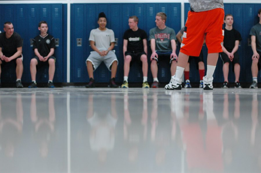 Photo by Hope Nicholas The Kalamazoo United Men's Lacrosse Team does wall sits at Four Corners in Loy Norrix. The team must do their conditioning in the hallways due to a lack of space elsewhere in the school.