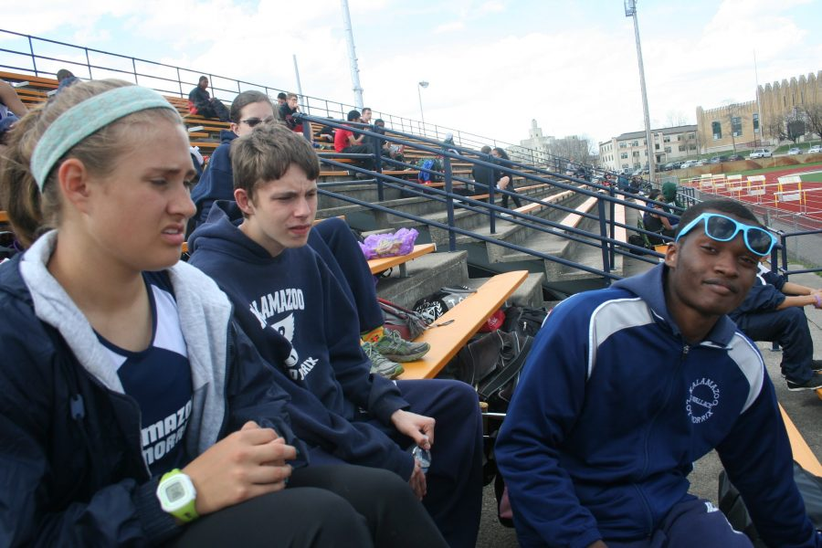 Sophomore Olivia VandePol, freshman Travis Grube, and Junior Darvious Wallace all sit and wait for a delayed track meet.