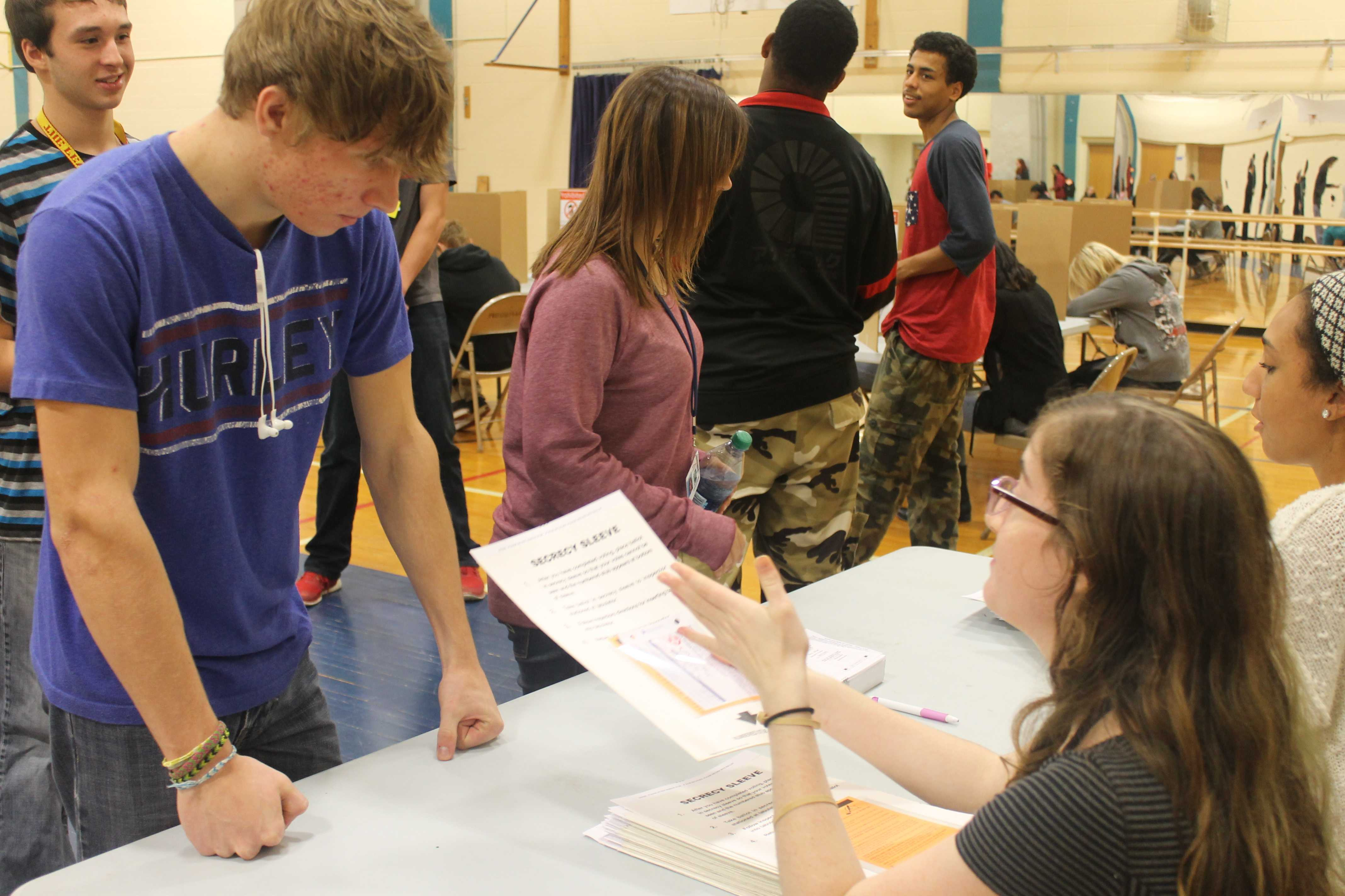 Loy Norrix students are given ballots as they prepare to vote. Mainly juniors and seniors  were invited to the election, though other students voted in their classrooms.  Photo credit:  Cori VanOstran