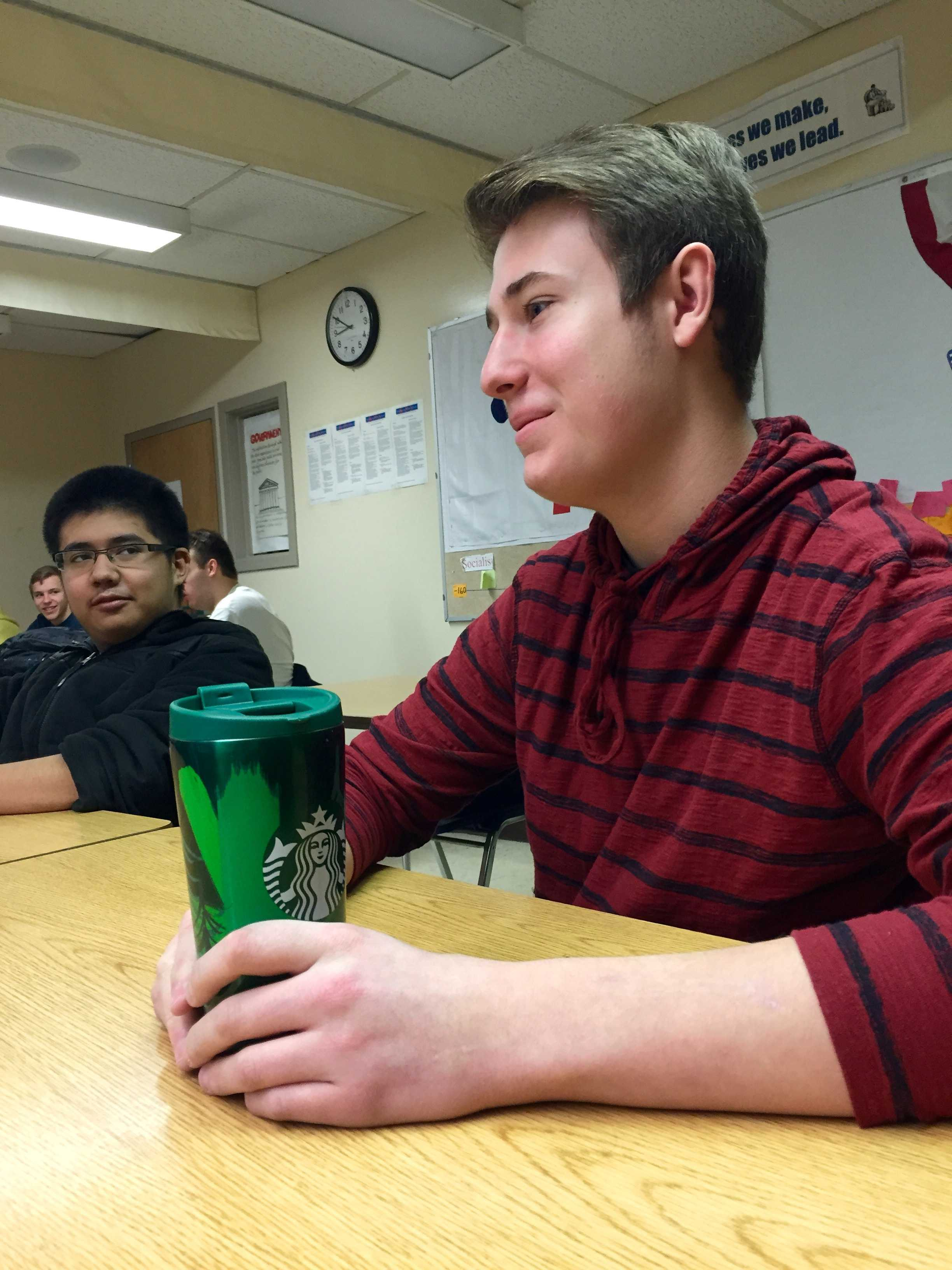 Junior Alex Lutz sits in his AP Government trying to pay attention to a powerpoint. Like many students Lutz drinks coffee in order to stay awake and stay focused in class.  Photo Credit / Hannah Stempky