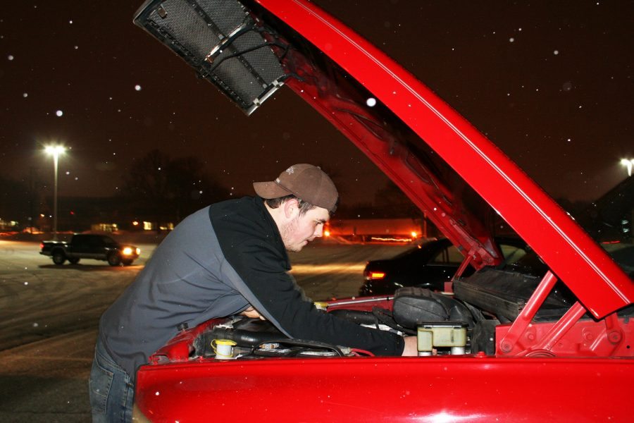 Junior Austin Herbert check his oil after his drive to school. He says how it is getting low, and once it gets too low the truck will start acting up.