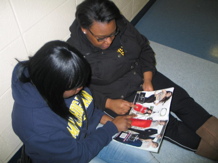 Seniors Melissa Lee and Zacara Savage look at a book of prom dresses together. They are deciding what style dress they want. Photo Credit / Evelyn Banks