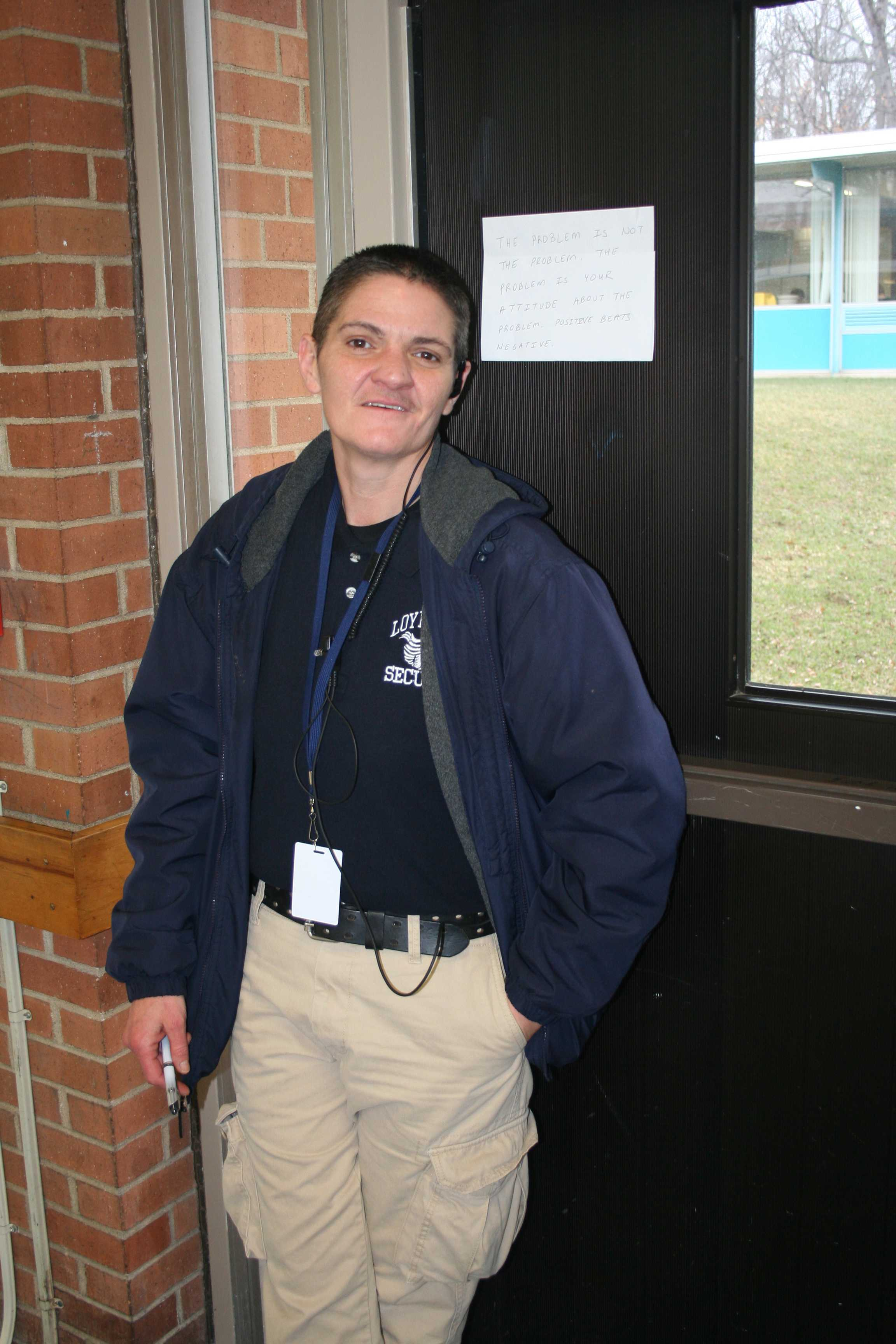 "Officer Codine stands guard in the halls. She is displaying a quote that says ""The problem is not the problem. The problem is your attitude about the problem. Positive beats negative."""