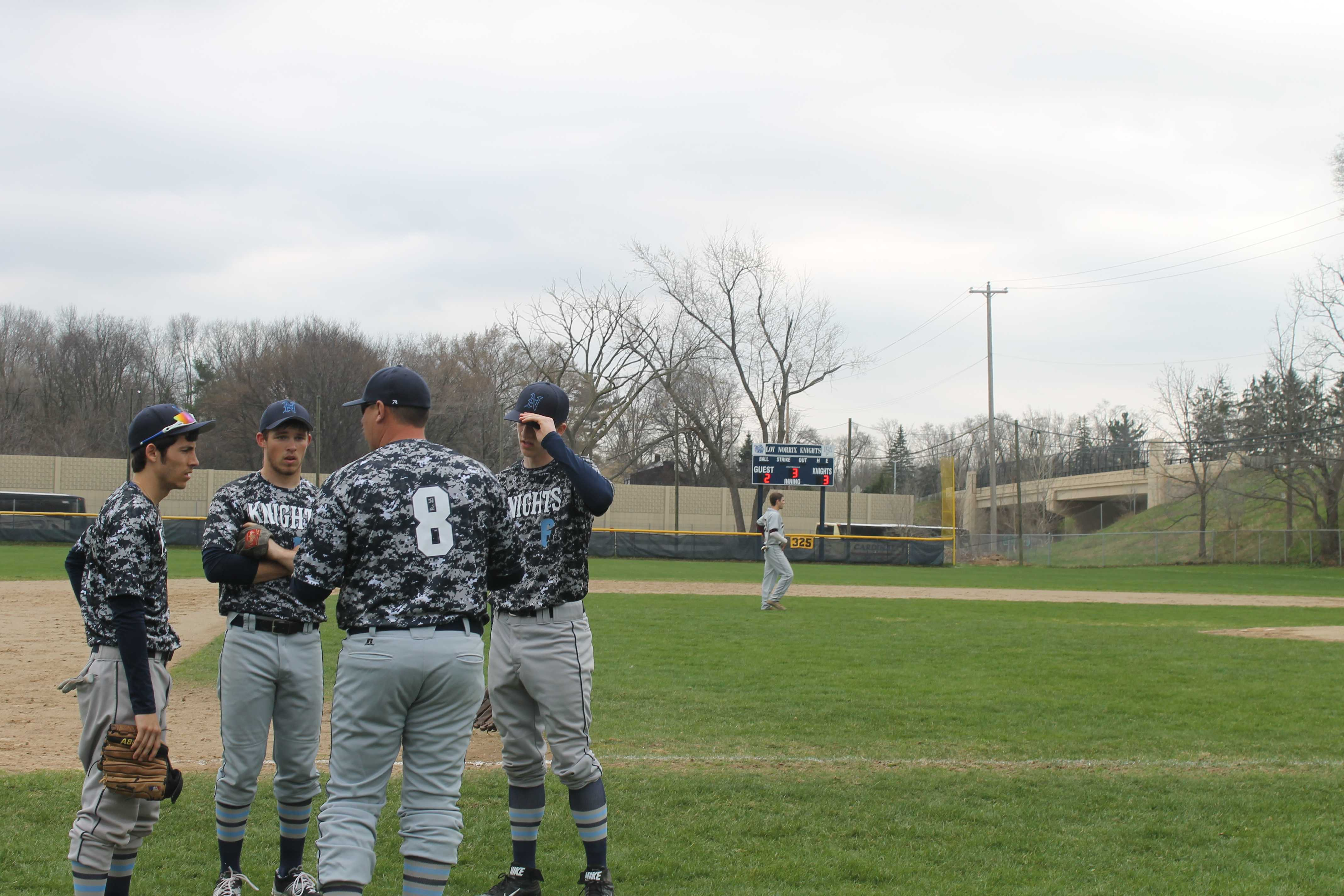 Coach Neel talks the last inning over with the outfielders. Photo Credit / Aj Rogers
