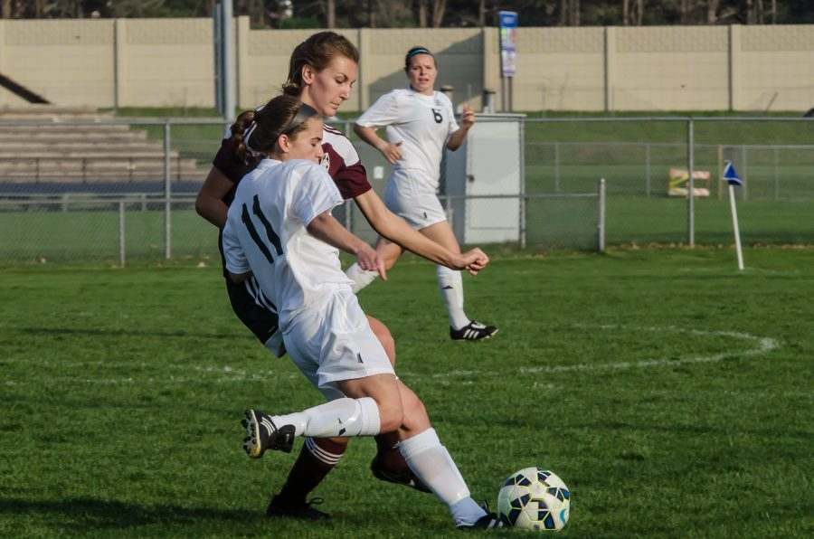 Sophomore Maria Egloff attempts to pass the ball t her teammate while under pressure from a Kalamazoo Central defender. Photo Credit / Deanne Puca