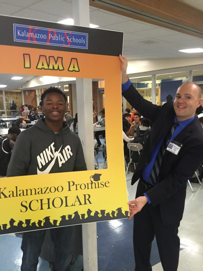 Aaron Holmes celebrates Promise Day, while Mr. Aguinaga holds the frame in front of him.