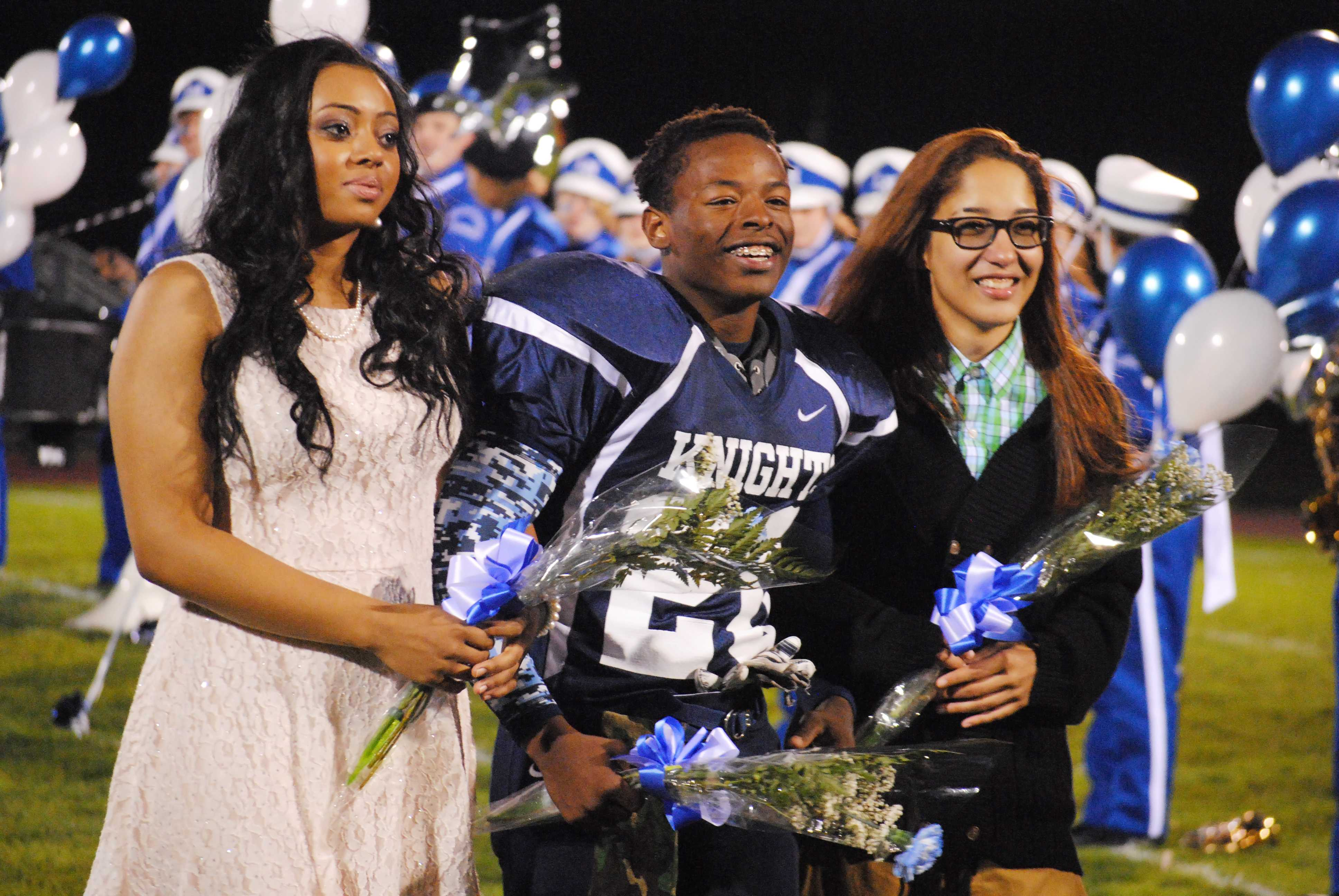 Seniors JeNessa Bogan, Aaron Holmes and Sabi Nieves walk down the decorated football field as part of the 2015 Homecoming Court. JeNessa Bogan and Sabi Nieves became the first same gendered King and Queen in Loy Norrix homecoming history. Photo Credit / Cori VanOstran