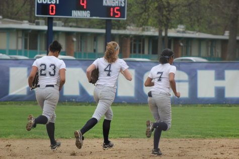 The three Loy Norrix outfielders run out to their positions in a game last spring. Many college coaches have had an eye on the three lady Knights. From Left to Right: #23 Keisha Harris, #4 Megan Lohner, #7 Maia Greer. Photo Credit / Kristi Johnson