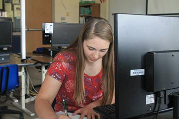 "Junior Lacey Burke sits in front of a computer doing her PreCalculus test on MIVHS. She is taking this class because it does not fit into her schedule. ""I enjoy the level of autonomy that I have when completing and turning in my assignments. I can make it work around my personal schedule,"" said Burke. Photo Credit / Grace Augustine"