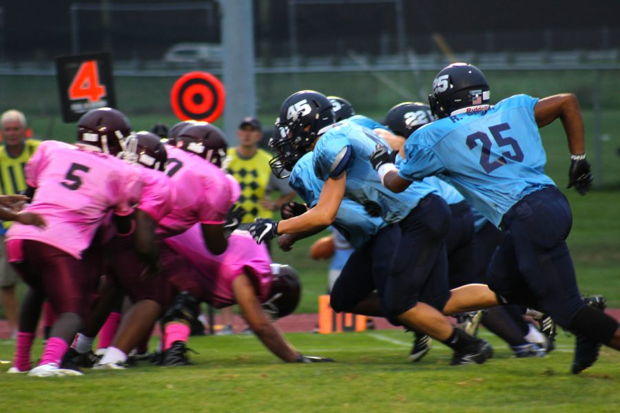 Loy Norrix (right) Kalamazoo Central (left) head off against each other on the night of September 9th 2016. The two teams wear donated jerseys for breast and prostate cancer cause. Photo Credit / Zach Liddel