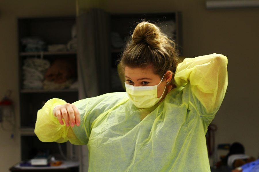 "Senior Grace Ritchie focuses on correct application and removal of personal protective equipment. Mrs Kuzmick watches Grace to make sure she knows how to put it on correctly and makes sure it's tied right. ""Putting on the PPE was difficult but all the practice helped a lot,"" said Ritchie. Photo Credit / Meghan Lewis"