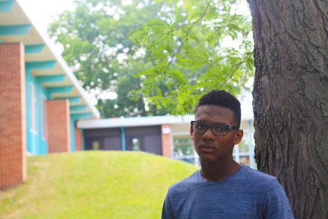 Malik Farrakhan posing in front of Loy Norrix High School. Photo Credit / Henry Snapp