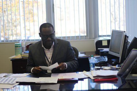 Johnny Edwards looks over new work that's been piling up since his arrival. On top of the new work as principal, he also has to tackle being the Director of Secondary Education. Photo Credit  / Brandon Schnurr