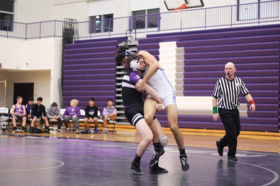 Junior Roy Britney is trying to escape the grip of his opponent from Battle Creek Lakeview. Britney has been in wrestling for almost 3 years and is now team captain. Photo Credit / Mia May