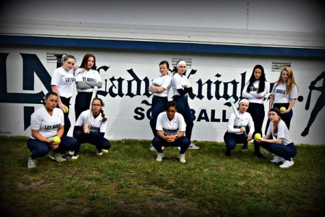 The varsity women's softball team pose for a picture in front of the dug-out. Photo Credit / Kristi Johnson