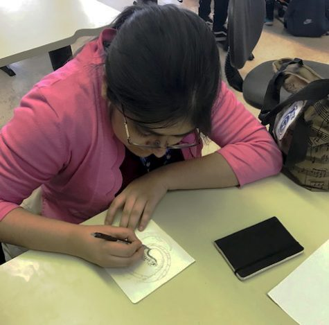 Jessica Armendariz Gallardo, a junior at Loy Norrix, draws a cartoon dragon circling through the surface of the water. By practicing cartooning, she hopes to refine her skills so that one day she will be able to translate her drawings to a T.V. screen. Photo Credit: Carly Loken