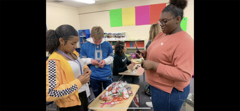 Sophomores Jayda Smith, Chanel Wilson, and  Anthony Porco all work to build candy bags. Creating the candy bags and selling them at lunches were an idea created by Wilson to raise money for homecoming.