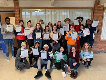 Participants in the Mental Health Awareness training hold up certificates of completion.