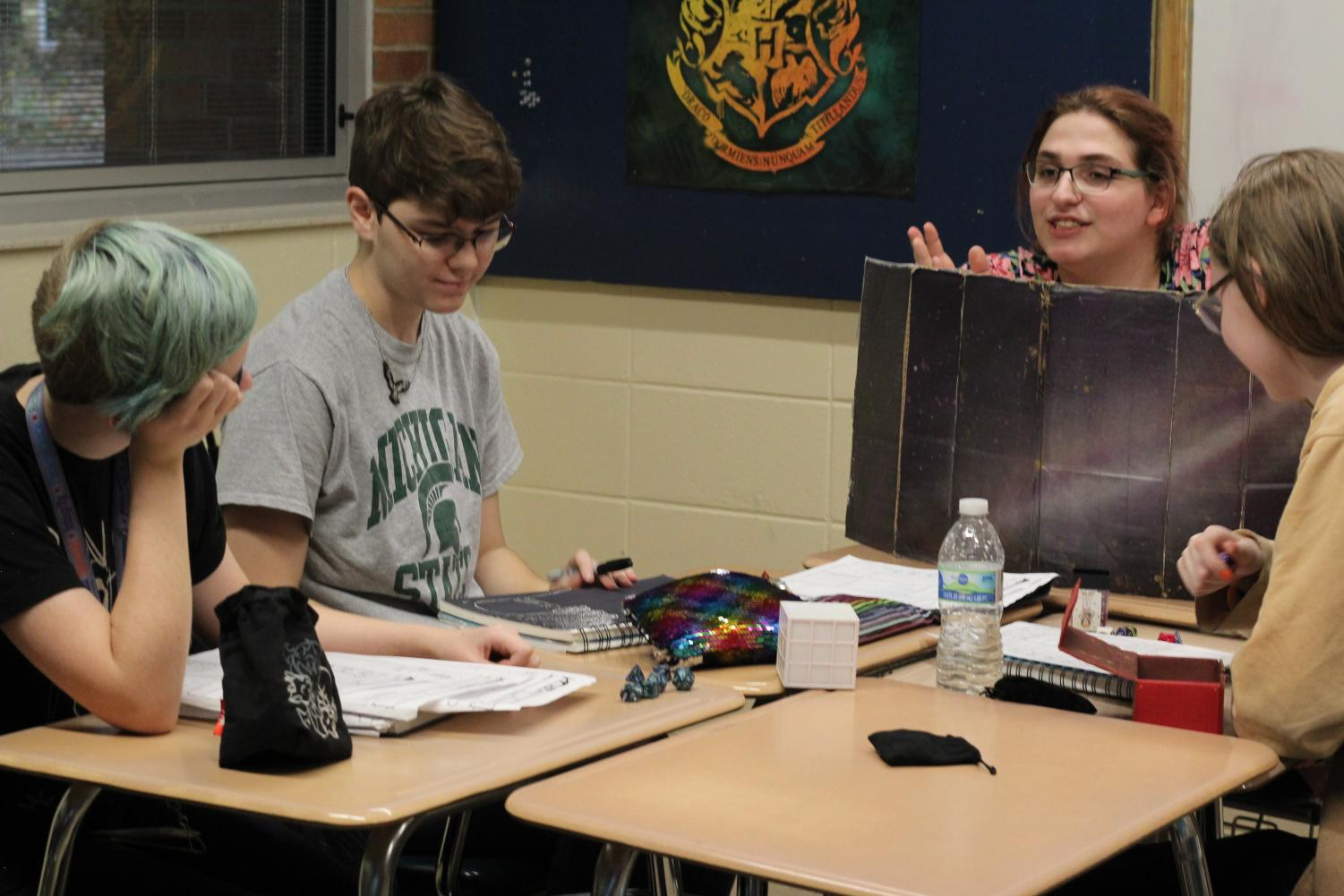 SWORD members Kai Neve-Jones, Asher Gilbert, and Dash DeGrote listen carefully as Dungeon Master Natalie Sweet paints the scene.  (Left to right: Kai Neve-Jones, Asher Gilbert, Natalie Sweet, and Dash Degrote)