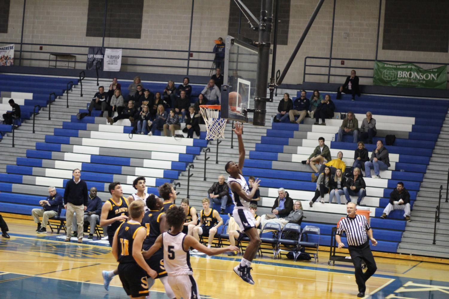 Varsity basketball player and senior Joshua Mabon Cooks recovers the ball and scores in the second quarter. Loy Norrix had a rough first quarter but pushed St. Joseph until the 4th quarter, going into overtime. Photo Credit / Colin Carnell