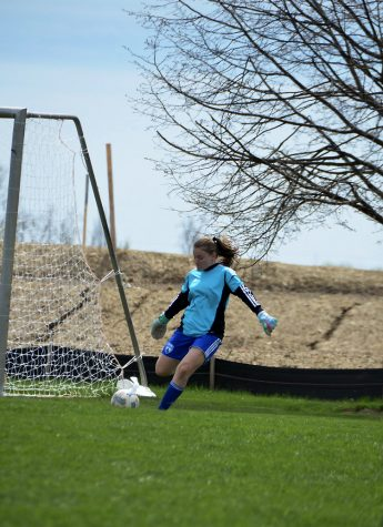 Goalie, Hannah Locke, kicks the soccer ball out from the net. Hannah played a big role during a big away-match.