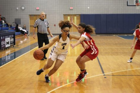Junior varsity and sophomore Vicky McGowan dribbles around her opponent in an attempt to score a basket. McGowan scored a total of eight points in the game against Grand Rapids Union high school.
