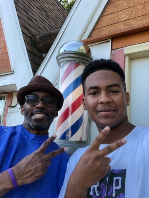 Junior Kaleb Madrigal poses for a photo with his mentor Paul Frazier in front of International Profyle Barbershop.
