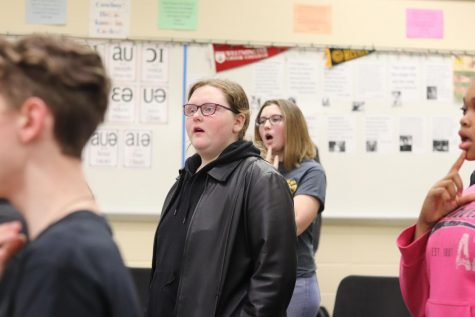 Jessica DeRyke sings in choir teacher Julie Pelligrino's class.  Despite challenges, DeRyke excels in her school work and finds joy in singing.