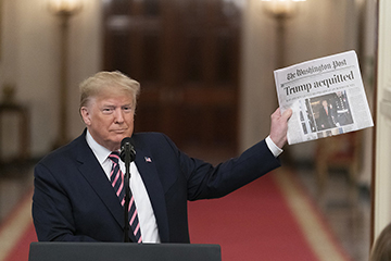 President Donald Trump holds up a copy of The Washington Post headlined with Trumps acquittal. President Trump was acquitted on February 5, 2020.