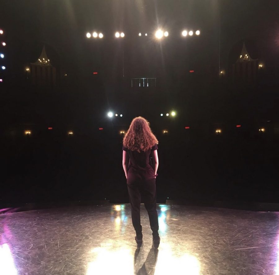 Senior Katie Kutzko stands on an empty stage, looking out at the empty theatre. The lights are still on from the show, but without an audience the theater is silent.