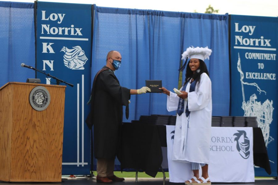 An early graduate from the class of 2020 receives their diploma at the graduation ceremony last year.
