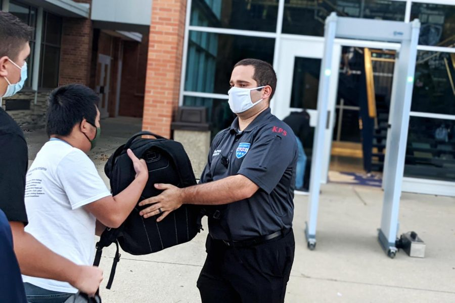 Campus safety officer pats down senior Jacob Shantzs bag. All students were searched for weapons before entering the building on Monday, September 27.