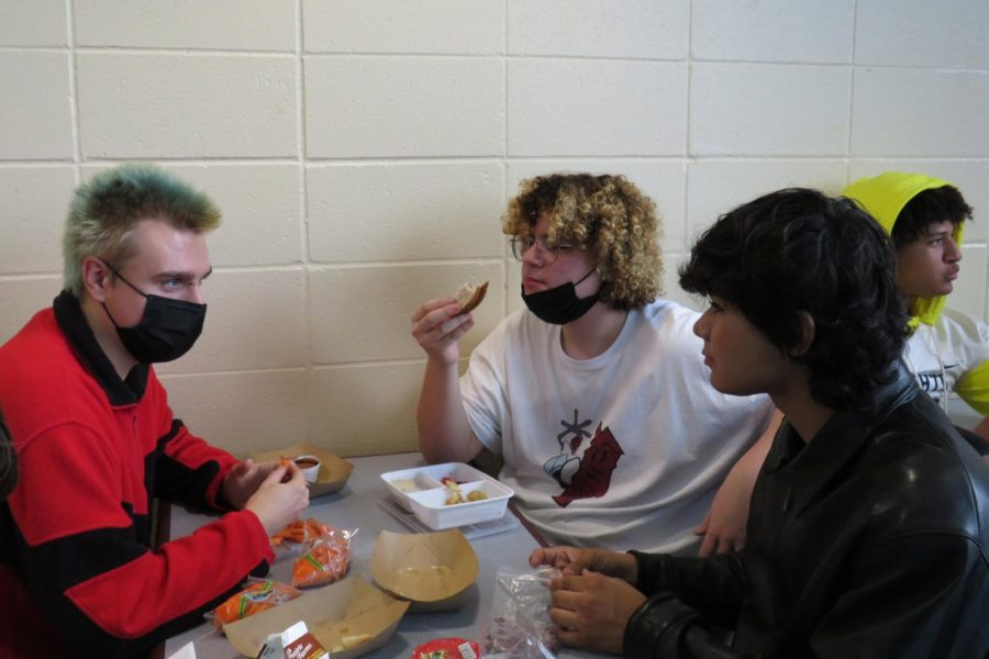 Senior Noah Doerschler, junior Wolfgang Madonia and sophomore Jackie Balderas chat during A-lunch.